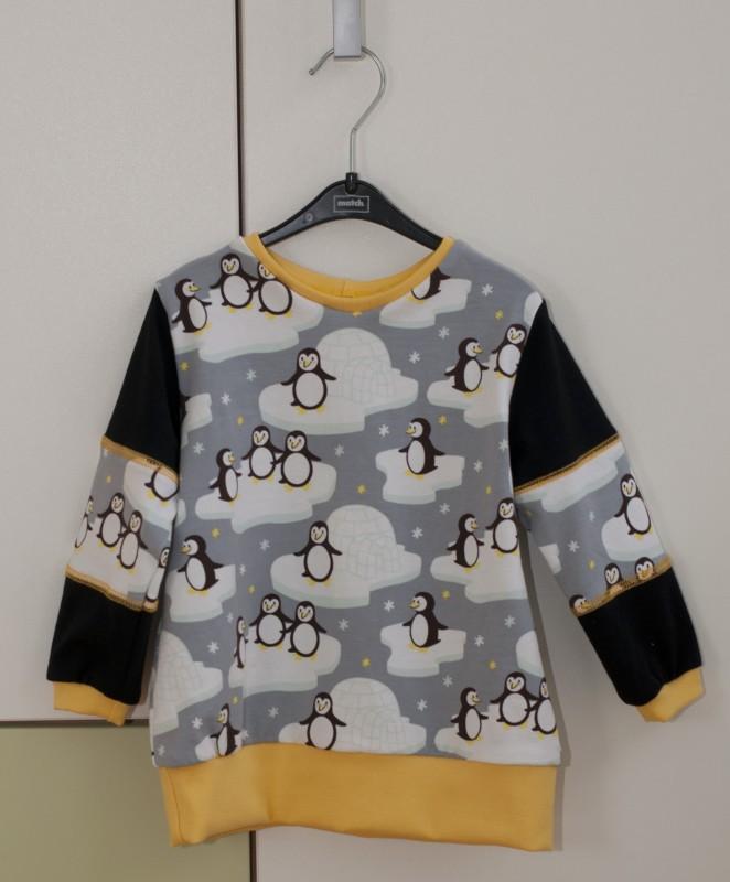 Pinguin-Pullover aus Pinguinstoff von Stoffwelten mit Ärmelteilungen und Covernähten am Kleiderschrank